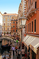 Tourists walking down Venice street with shops, restaurants. Traditional medieval lamp.