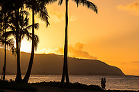 A man and woman enjoy the view at sunset, Hale'iwa Ali'i Beach Park, North Shore, O'ahu.