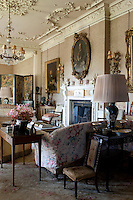 Gilt-framed portraits grace the fabric covered walls of the 17th century drawing room which features an ornamental plasterwork ceiling