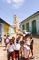 School children playing in cstreet scene with old church of the old colonial city of Trinidad in Cuba
