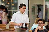 A waiter serves customers at a restaurant and cafe in Covent Garden, London.