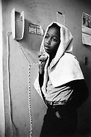 """USA. New York City. Spanish Harlem. Willie is talking on the telephone while his head and hair are covered by a white towel. The Puerto Rican family lives below the poverty line and receives public assistance (AFDC, Home Relief, Supplemental Security Income and Medicaid). The family resides in units managed by the New York City Housing Authority (NYCHA) which provides housing for low income residents. NYCHA administers rental apartments in facilities, popularly known as """"projects"""". Spanish Harlem, also known as El Barrio and East Harlem, is a low income neighborhood in Harlem area. Spanish Harlem is one of the largest predominantly Latino communities in New York City. 15.06.86 © 1986 Didier Ruef . ..."""