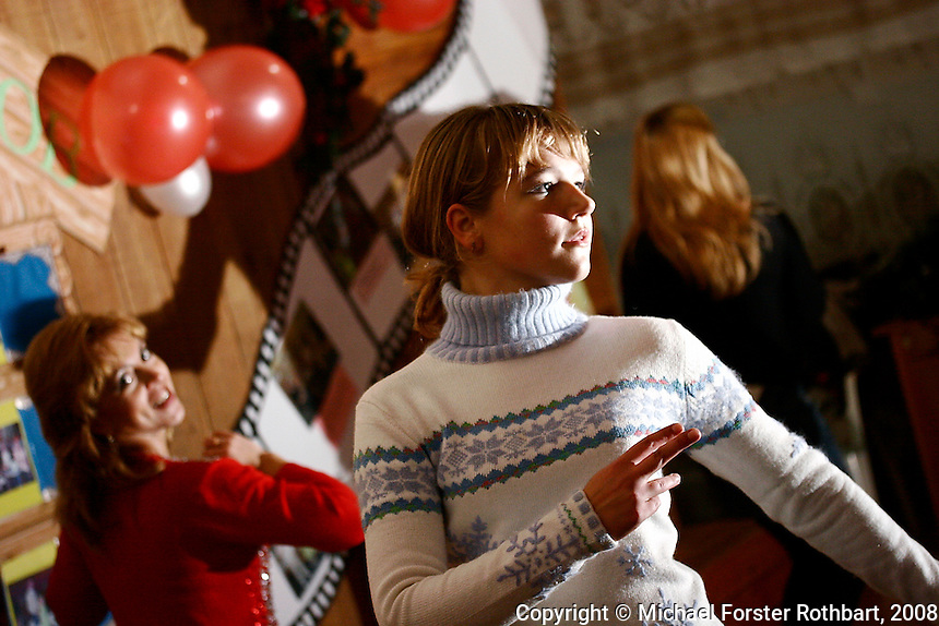 Dance and music teacher Lesya Kostenko (left) leads a dance rehearsal at the Chernobyl Community Center in Borodyanka, Ukraine. Her students, 14-year-olds Ira Dovstenka and Olya Shvitka, are from the resettlement village Nove Zalissya.  <br /> ------------------- <br /> This photograph is part of Michael Forster Rothbart's After Chernobyl documentary photography project.<br /> © Michael Forster Rothbart 2007-2010.<br /> www.afterchernobyl.com<br /> www.mfrphoto.com <br /> 607-267-4893 o 607-432-5984<br /> 5 Draper St, Oneonta, NY 13820<br /> 86 Three Mile Pond Rd, Vassalboro, ME 04989<br /> info@mfrphoto.com<br /> Photo by: Michael Forster Rothbart<br /> Date:  10/2008    File#:  Canon 20D digital camera frame 10694 <br /> ------------------- <br /> Original caption: .Dance and music teacher Lesya Kostenko leads a dance rehearsal at the Chernobyl Community Center in Borodyanka, Ukraine. Her students, Ira Dovstenka (in white), Olya Savechenko (singing) and Olya Shvitka (in black) are all 14-year-old girls from the village Nove Zalissya, 7 kilometers away. Borodyanka is a small town (population 16,000) 30 miles west of Kyiv and 48 miles south of the Chernobyl nuclear power plant, where many Chernobyl evacuees were resettled in 1986..-------------------.