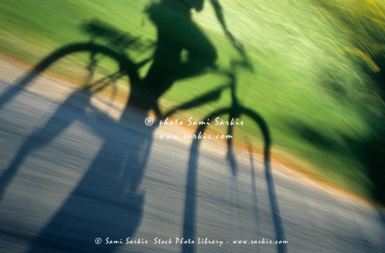 Speeding cyclist's shadow on the road
