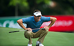 Robert Allenby lining up a putt on the eighth green during Round 1 of the CIMB Asia Pacific Classic 2011.  Photo © Raf Sanchez / PSI for Carbon Worldwide
