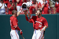 Evan Edwards (18) of the North Carolina State Wolfpack knocks helmets with teammate Brock Deatherage (13) after hitting a home run against the Army Black Knights at Doak Field at Dail Park on June 3, 2018 in Raleigh, North Carolina. The Wolfpack defeated the Black Knights 11-1. (Brian Westerholt/Four Seam Images)