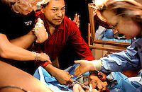 """Medical staff and interpreters guide an excited Roy Rios in cutting the umbilical cord of his new daughter, Shanice Morgan-Rios.  """"I hope my baby is not born deaf-blind with Usher's syndrome, like me,"""" said Rios, who is deaf-blind and has three other siblings with the disease.  Usher's is hereditary.; there is no trreatment or cure.  Rios already has a son, who was born without Usher's.  Tests show that his daughter is able to hear.  Doctors will test her later to determine whether she has any vision problems."""
