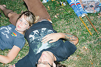 Deb Ennis, 26, and her fiance Keith Traister, 23, both of Michigan, relax on the ground in the protest area in FDR Park outside of the secure area surrounding the Democratic National Convention at the Wells Fargo Center in Philadelphia, Pennsylvania, on Wed., July 27, 2016. The two had rollerbladed and walked from central Philadelphia to the protest area during the day.  The two have been staying with a Trump supporter who opened his house to them through Craigslist after the pair couldn't find a camping spot for their time in Philadelphia.
