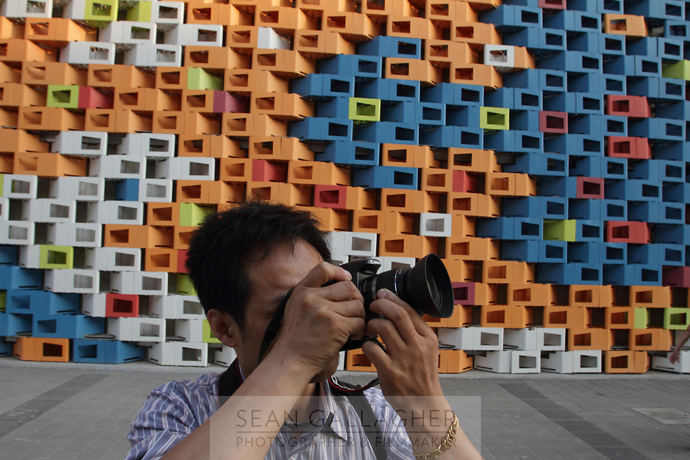 A man takes a picture in front of an elaborately designed pavilion at the Shanghai World Expo.