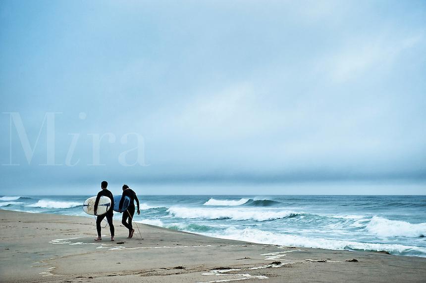 Two surfers walk along the beach, Nauset Beach, Cape Cod, MA, USA