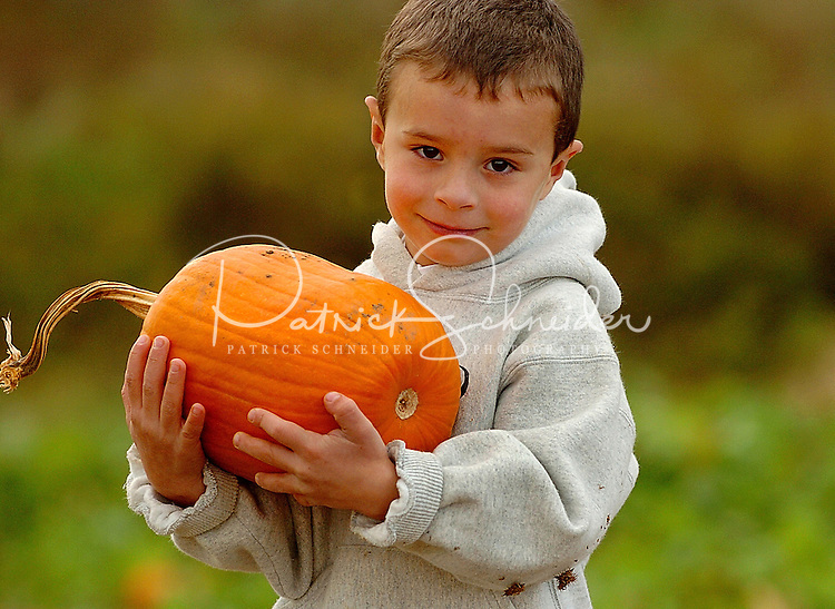 A young boy shows off the perfect Halloween pumpkin he selected during his visit to a pumpkin patch in North Carolina.