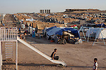 DOMIZ, IRAQ: Children play on a slide in the Domiz refugee camp...Over 7,000 Syrian Kurds have fled the violence in Syria and are living in the Domiz refugee camp in the semi-autonomous region of Iraqi Kurdistan...Photo by Ali Arkady/Metrography