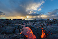 At sunset, visitors marvel at the glowing molten lava flowing down the hill while sun rays beam through distant clouds, Hawai'i Volcanoes National Park, Hawai'i Island.