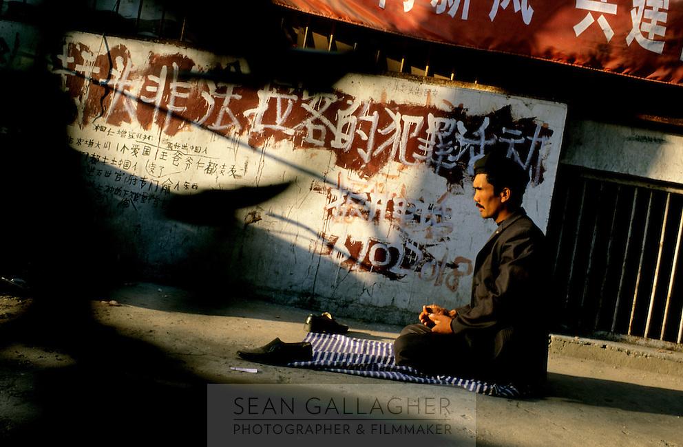 CHINA. Beijing. A Uighur Mulsim prays in a back-alley near Tiananmen Square. 2005