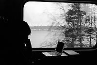 Switzerland. Canton Vaud. Grandson. A lonely woman, seated in an inter-city train, looks at the lake Neuchâtel. A portable computer, Mac Book Pro, is on the table. Inter-city rail services are express passenger train services that cover longer distances than commuter or regional trains. An inter-city train is an express train with limited stops and comfortable carriages to serve long-distance travel. 15.10.12 © 2012 Didier Ruef