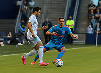 KANSAS CITY, KS - MAY 29: Luis Martins #36 of Sporting KC begins his team's drive upfield as Zarek Valentin #4 of Houston FC keeps the pressure on him during a game between Houston Dynamo and Sporting Kansas City at Children's Mercy Park on May 29, 2021 in Kansas City, Kansas.