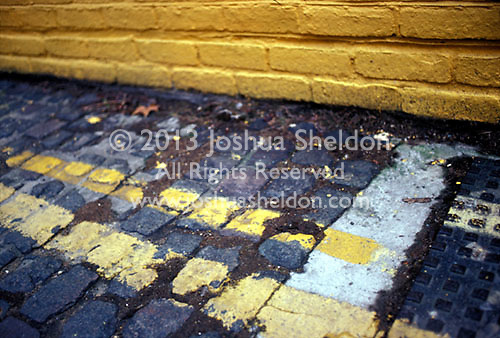 Close up of yellow paint on street with yellow painted brick wall<br />