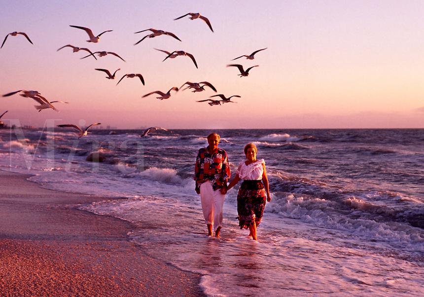 A senior couple walks on the beach at sunset.