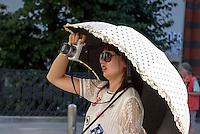 asiatische Touristin mit Sonnenschirm fotografiert im Innenhof Alte Hofburg, Wien, Österreich<br /> Tourist with parasol taking pictures, Vienna, Austria