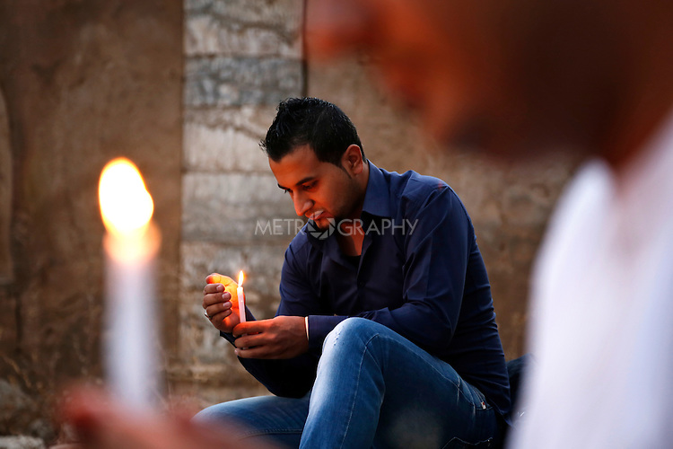 KIRKUK, IRAQ: People attend a candlelit vigil at the ruins of the Chaldean church in Kirkuk on the third anniversary of the attack on the Our Lady of Salvation church n Baghdad.  A mix of Christian and Muslim youth gathered to pay their respects.<br /> <br /> On the 31st October 2010 militants attacked the Our Lady of Salvation catholic cathedral in Baghdad taking worshippers hostage.  By the time they were released 58 people had been killed.  Kirkuk lies in the area of Iraq which is disputed territory with both the central Baghdad government and the semi-autonomous Kurdish Regional Government laying claim to it.<br /> <br /> Photo by Mohammed Abdullah/Metrography