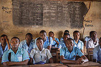 Nigeria. Enugu State. Enugu. Army Day Secondary School ( Awkunanaw in Igbo language). Classroom. Igbo students during a class about Citizenship and Civic Education. The pupils, boys and girls,  wear blue uniforms. They are 15-16 years old. They belong to the class SS2F, Senior Secondary School. The Army Day Secondary School was inaugurated in October 1998. Blackboard with weekly schedule and chalk writings. Enugu is the capital of Enugu State, located in southeastern Nigeria. 11.07.19 © 2019 Didier Ruef