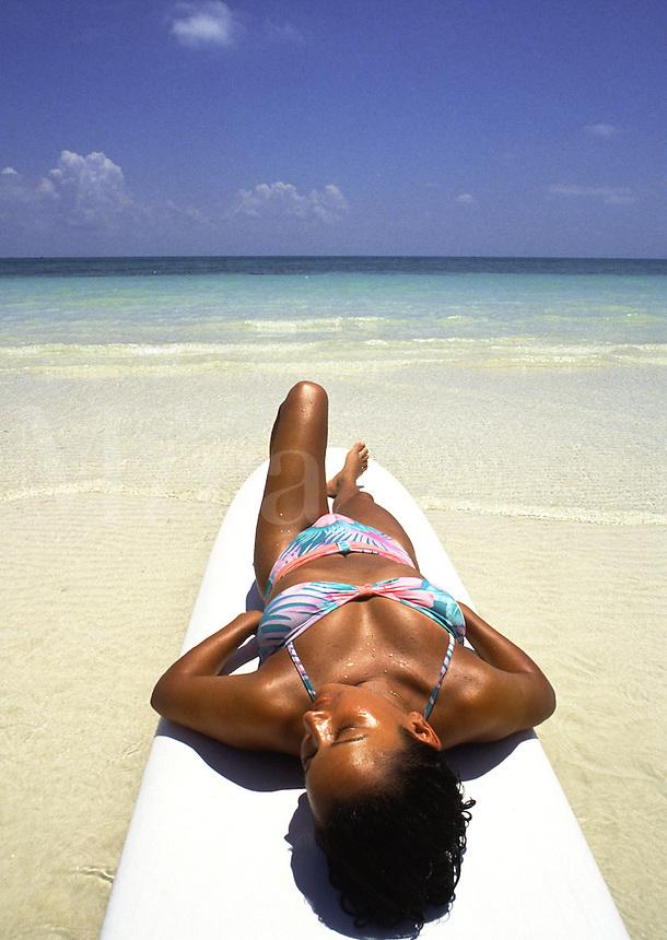 African-american woman sunbathing on surfboard on beach