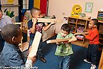 Education preschool 4 year olds group of boys aiming long blocks of wood like guns