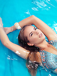 Portrait of a beautiful young woman with blond hair wearing a swimsuit lying in blue water Image © MaximImages, License at https://www.maximimages.com