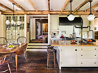 A dropped floor makes the kitchen feel more expansive. The stove hood was custom-made and the<br /> island pendant is from Circa Lighting. The flooring is reclaimed antique oak planks.