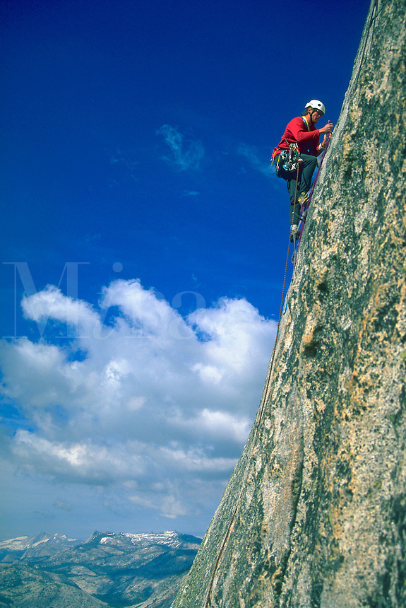 A climber making a one day ascent of the steep rocky face of Half Dome in Yosemite National Park, California with mountains, blue sky and clouds in the distance.