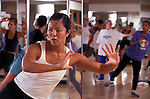 young woman instructor leading aerobics class seen in mirror behind her in health club studio