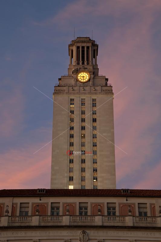 Austin university clock tower during evening pink sunset in downtown Austin, Texas, USA.
