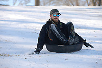 Andrew Newton (center) of Prairie Grove reaches to steady himself Friday, Feb. 19, 2021, as he slides downhill in an animal feed trough while sledding with his family at Battlefield State Park in Prairie Grove. The Newtons were taking a break from virtual instruction to take advantage of the good sledding conditions before warm temperatures melted the snow from the hillside. Visit nwaonline.com/210220Daily/ for today's photo gallery. <br /> (NWA Democrat-Gazette/Andy Shupe)