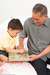 3 year old preschool age boy with grandfather playing with toy puzzle maze, assisting him by holding it level and talking to him