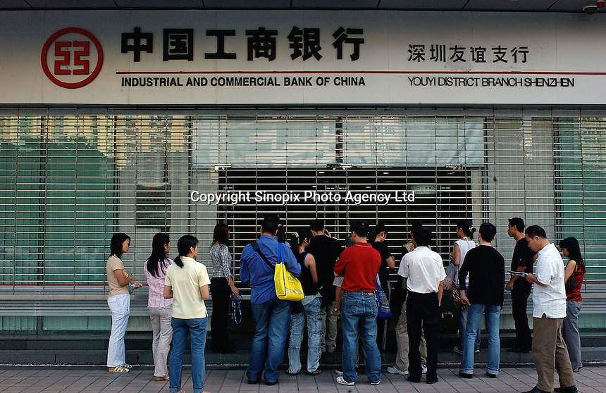 Customers wait outside the Industrial and Commercial Bank of China, in Shenzhen, China. .