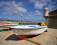 Boats on the beach at Lagos, with the old harbour defenses, the 17th century Forte Bandeira, under a deep blue and partly cloudy sky, Algarve, Portuga