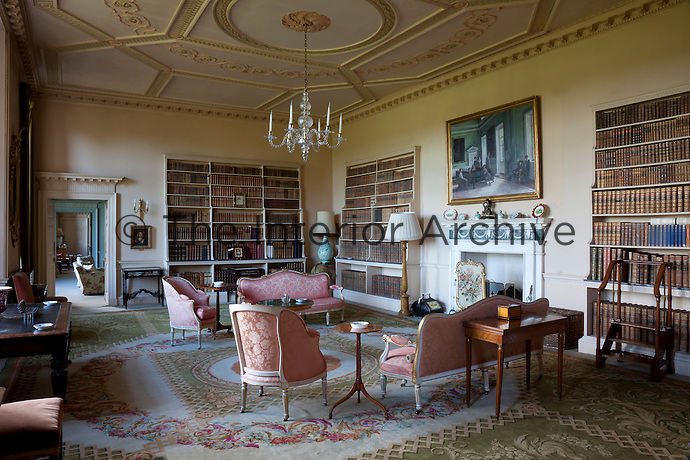 The books in the library are stored on tiered bookcases. A portrait of the Naylor-Leyland family in the green long gallery hangs above the fireplace