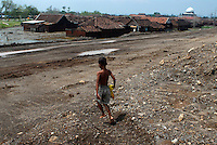 A child runs down towards the submerged Besuki village. Diggers continue building up the earthen dam walls that are stopping the mud flow from expanding. Since May 2006, more than 10,000 people in the Porong subdistrict of Sidoarjo have been displaced by hot mud flowing from a natural gas well that was being drilled by the oil company Lapindo Brantas. The torrent of mud - up to 125,000 cubic metres per day - continued to flow three years later.