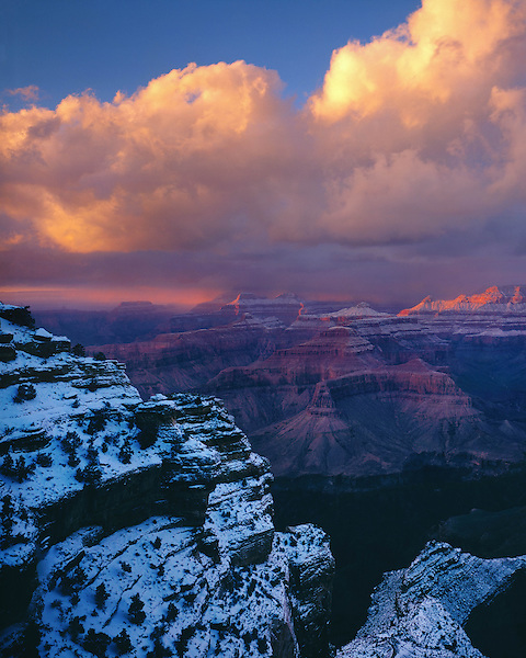 Sunburst during a snowstorm along the South Rim of Grand Canyon National Park, northern Arizona, USA. .  John offers private photo tours in Grand Canyon National Park and throughout Arizona, Utah and Colorado. Year-round.
