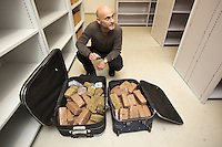 """Switzerland. The Republic and Canton of Neuchâtel. Neuchâtel. The commissar Manuel Garcia at the police station headquaters. The narcotics squad during """"Narko"""" operation has seized two luggages full of cannabis (6 kg) and hashich (21 kg). The narcotics squad works in plainclothes. Plainclothes law enforcement is a method used by police. The policemen wear plainclothes or """"ordinary clothes"""" instead of a uniform in order to avoid detection or identification as law enforcement agents. Cannabis, commonly known as marijuana, is a preparation of the Cannabis plant intended for use as a psychoactive drug. Pharmacologically, the principal psychoactive constituent of cannabis is tetrahydrocannabinol (THC); it is one of 483 known compounds in the plant, including at least 84 other cannabinoids, such as cannabidiol (CBD), cannabinol (CBN), tetrahydrocannabivarin (THCV), and cannabigerol (CBG). Hashish, or hash, is a cannabis product composed of compressed or purified preparations of stalked resin glands, called trichomes. It contains the same active ingredients—such as tetrahydrocannabinol (THC) and other cannabinoids—but often in higher concentrations than unsifted buds or leaves. 31.03.15 © 2015 Didier Ruef"""