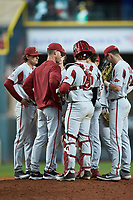 Arkansas Razorbacks pitching coach Matt Hobbs has a meeting on the mound during the game against the Texas Longhorns in game six of the 2020 Shriners Hospitals for Children College Classic at Minute Maid Park on February 28, 2020 in Houston, Texas. The Longhorns defeated the Razorbacks 8-7. (Brian Westerholt/Four Seam Images)
