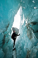 """Young woman in the ice cave or as glacier guides call it """"iris"""" on Franz Josef Glacier - Westland National Park, West Coast, New Zealand"""