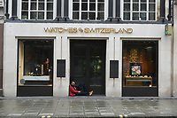 A man sits in the doorway of the Watches of Switzerland store in Oxford Street. The deserted streets show the severe effects of the COVID-19 epidemic on London on the morning of 19th March 2020