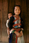 Hmong Hill Tribe Northern Thailand South East Asia.  Young girl her baby sister screams in a sling on her back Pa Kludy village 1990s