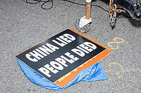 """Signs reading """"China Lied / People Died"""" lay on the ground as people gather for an anti-lockdown protest organized by the alt-right group Super Happy Fun America near the home of Massachusetts governor Charlie Baker in Swampscott, Massachusetts, on Sat., May 16, 2020. The protest was in defiance of Massachusetts orders mandating face coverings and social distancing and prohibiting gatherings larger than 10 people during the ongoing Coronavirus (COVID-19) global pandemic. The state's stay-at-home order is expected to be updated on May 18, 2020, with a phased reopening plan issued by the governor as COVID-19 cases continue to decrease. Anti-lockdown protests such as this have become a conservative cause and have been celebrated by US president Donald Trump. Many of the protestors displayed pro-Trump messages or wore Trump campaign hats and shirts with phrases including """"Trump 2020"""" and """"Keep America Great."""" Super Happy Fun America, organizers of the protest, are an alt-right organization best known for creating the 2019 Boston Straight Pride Parade."""