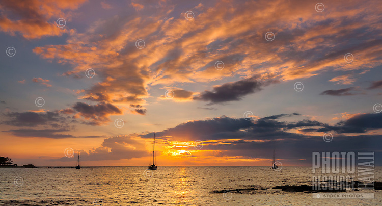 At sunset, three sailboats remain anchored in Puako Bay on the Big Island.