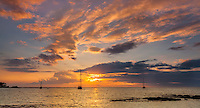 At sunset, three sailboats remain anchored in Puako Bay on the Big Island.
