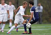 HYATTSVILLE, MD - OCTOBER 26, 2012:  James Gielen (26) of DeMatha Catholic High Schoolslips the ball past Arjan Ganji (10) of St. Albans during a match at Heurich Field in Hyattsville, MD. on October 26. DeMatha won 2-0.