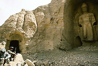 Two Hazara Mujahedin's at the Kakrak  Buddha 6 meters statue in 1996..In the Kakrak Valley, 2 kilometres south of the giant Bamiyan Buddha cliff , there is a 6 meters standing Buddha in a niche which was discovered in 1930. The Buddha niche is also surrounded by caves but the paintings were painstakingly removed by French archaeologists..Some scholars consider these mystic diagrams from Kakrak to be the earliest specimens of the type of cosmic Mandala found today in Nepal and Tibet.
