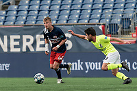 FOXBOROUGH, MA - MAY 12: Sean O'Hearn #40 of New England Revolution II looks to pass as Austin Panchot #12 of Union Omaha closes during a game between Union Omaha and New England Revolution II at Gillette Stadium on May 12, 2021 in Foxborough, Massachusetts.